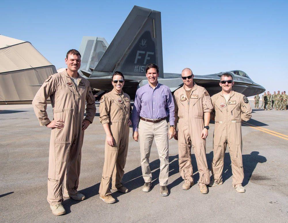 El secretario de Defensa Mark Esper, con la camisa azul, se encuentra con los aviadores frente a un F-22 Raptor en la Base Aérea Prince Sultan a principios de octubre.