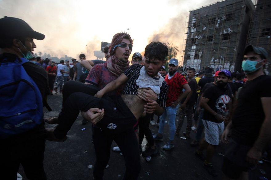Un manifestante iraquí lleva a un compañero herido durante una manifestación contra la corrupción estatal, el fracaso de los servicios públicos y el desempleo en la plaza Tayaran en Bagdad el 2 de octubre de 2019. (AHMAD AL-RUBAYE / AFP)