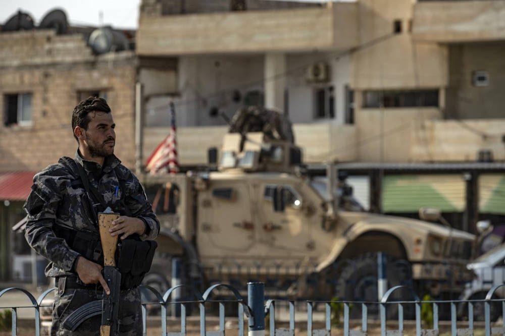 Un combatiente de las Fuerzas Democráticas Sirias SDF hace guardia mientras un vehículo militar estadounidense que sale de una base de las fuerzas estadounidenses en la ciudad siria del norte de Tal Tamr pasa el 20 de octubre de 2019 (Delil SOULEIMAN / AFP)