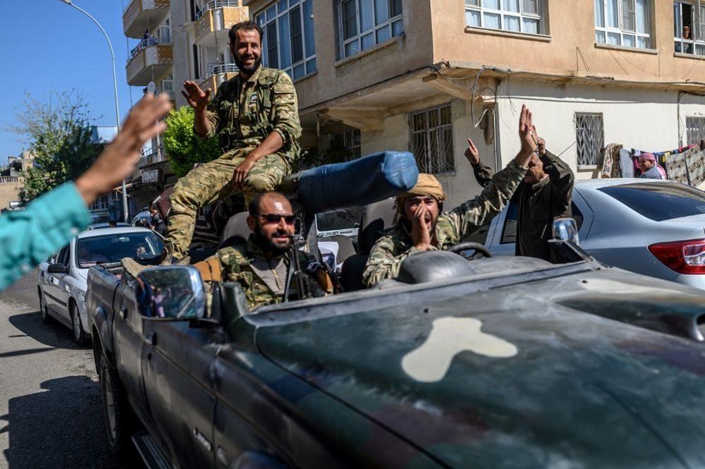 Los combatientes de la oposición siria respaldados por Turquía van a Tel Abyad desde la puerta turca hacia Siria en Akcakale en la provincia de Sanliurfa el 10 de octubre de 2019. (BULENT KILIC / AFP)
