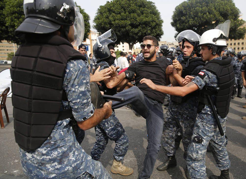 La policía retira a un manifestante antigubernamental que bloquea una carretera principal con su cuerpo en Beirut, Líbano, 26 de octubre de 2019 (Foto AP / Hussein Malla)
