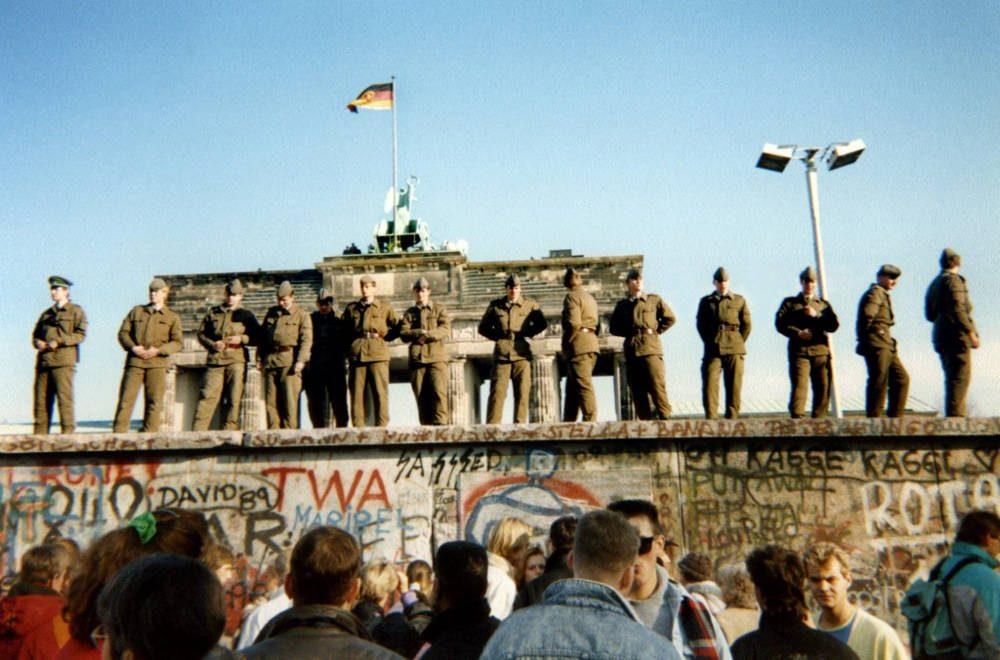 En esta foto de archivo tomada el 11 de noviembre de 1989, los guardias fronterizos de Alemania Oriental se paran en una sección del muro de Berlín con la puerta de Brandenburgo al fondo en Berlín. (Gunther Kern / AFP)