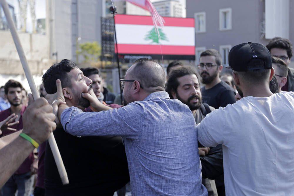 Los partidarios de Hezbolá, en primer plano, luchan con un manifestante antigubernamental durante los enfrentamientos que surgieron entre ellos durante las protestas en curso contra el gobierno libanés en Beirut, Líbano, 29 de octubre de 2019 (AP Photo / Hassan Ammar)