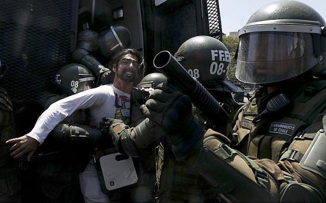 Un manifestante patea un bote de gas lacrimógeno durante los enfrentamientos con la policía en Santiago, Chile, 20 de octubre de 2019. (Foto AP / Esteban Felix)
