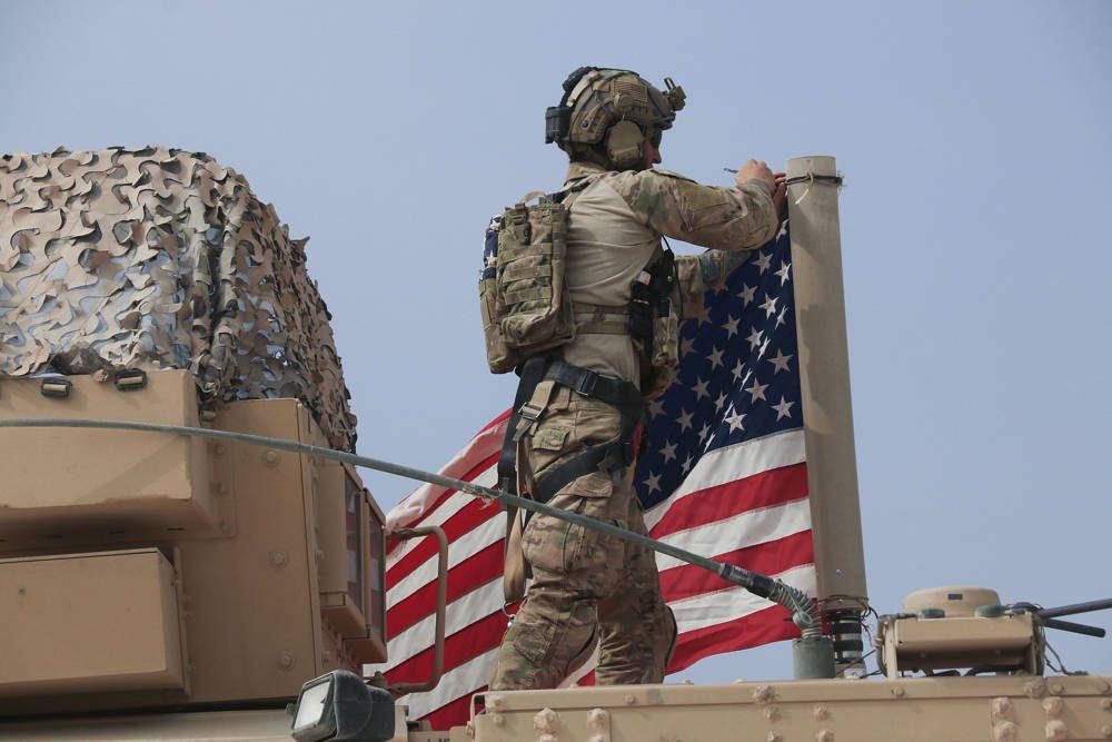 Soldado estadounidense monta la bandera estadounidense en un vehículo cerca de la ciudad de Tel Tamr, norte de Siria, el domingo 20 de octubre de 2019. (Foto AP / Baderkhan Ahmad)