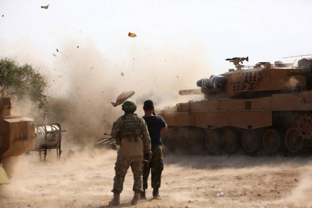 Soldados turcos en una posición al este de la ciudad siria nororiental de Ras al-AIn observan cómo un tanque dispara en las posiciones mantenidas por combatientes del Ejército Democrático Sirio (SDF) el 28 de octubre de 2019. (Nazeer Al-khatib / AFP)
