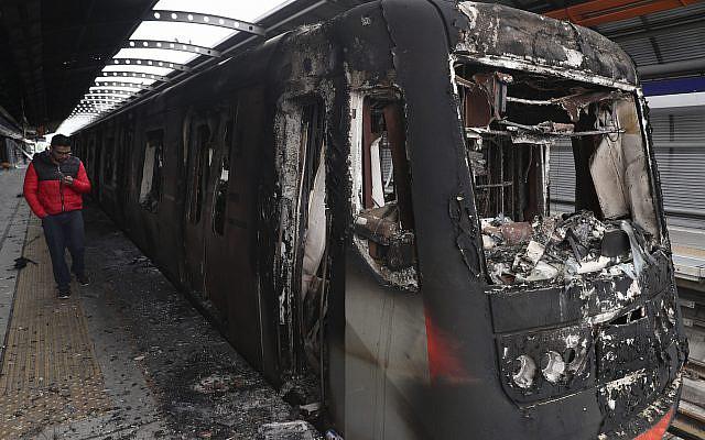 Los vagones del metro quemados por los manifestantes están estacionados en la estación Elisa Correa en Santiago, Chile, 20 de octubre de 2019. (Foto AP / Esteban Felix)