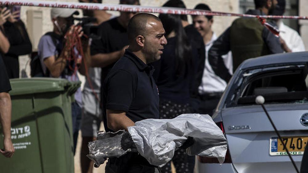Un zapador de la policía lleva un cohete explotado desde la casa que golpeó en Netivot, el 12 de noviembre de 2019.