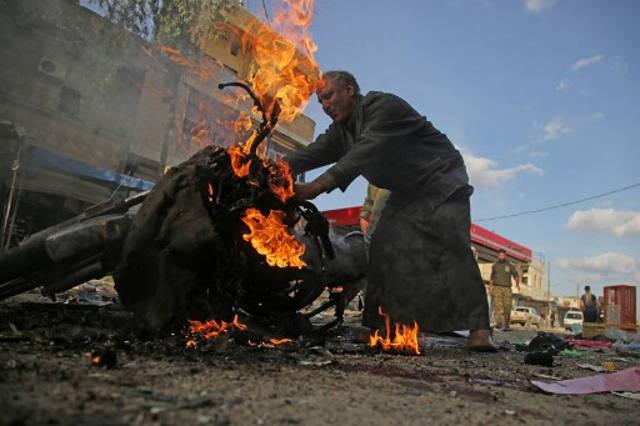 Un hombre sirio se encuentra junto a una motocicleta en llamas en el lugar de la explosión de un coche bomba en la ciudad kurda de Tal Abyad, en el norte de Siria, en la frontera con Turquía, el 2 de noviembre de 2019. (Bakr Alkasem / AFP)