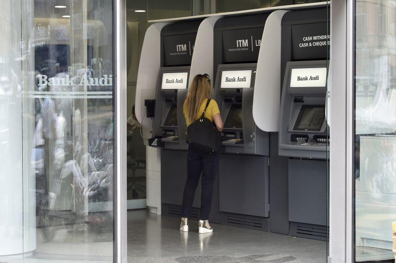 Las mujeres usan cajeros automáticos en el banco Blom en Beirut, Líbano, 1 de noviembre de 2019. Fotografía tomada a través del vidrio. REUTERS / Goran Tomasevic
