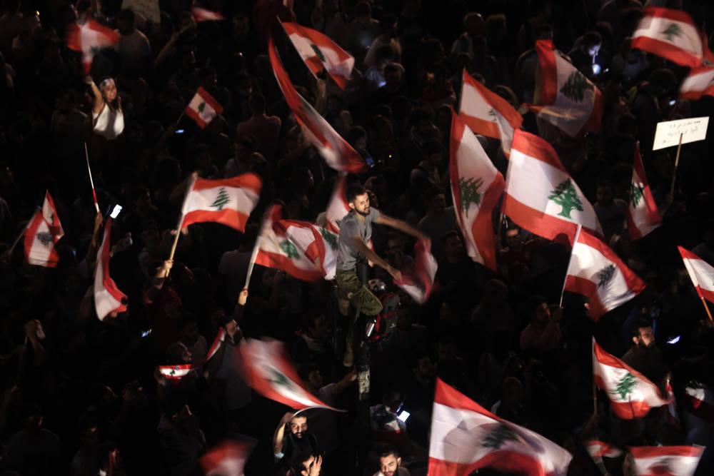 """En esta foto de archivo del 21 de octubre de 2019, los manifestantes antigubernamentales ondean banderas libanesas y cantan: """"la gente quiere derrocar al régimen"""" fuera de la oficina del legislador Mohammed Raad, el poderoso jefe del bloque parlamentario de Hezbolá, en Beirut, Líbano. (Foto AP / Hassan Ammar, archivo)"""