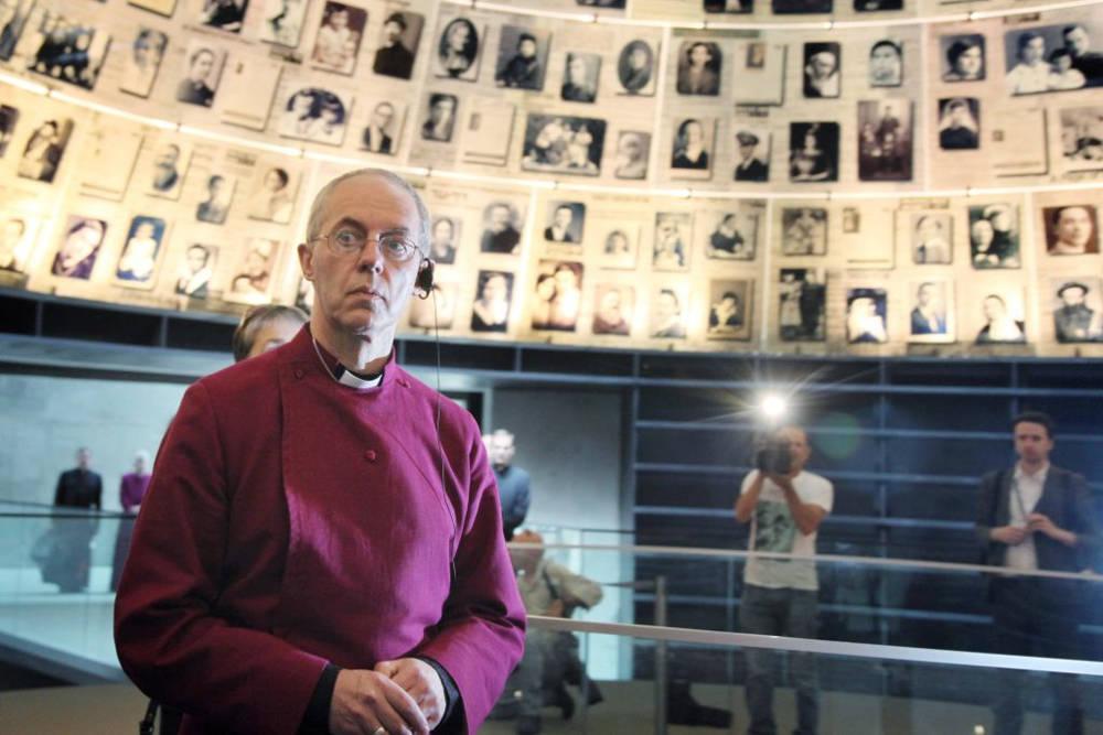 El actual arzobispo de Canterbury y obispo principal de la Iglesia de Inglaterra, Justin Welby, mira hacia arriba y a su alrededor fotografías de víctimas individuales del Holocausto en el Salón de los Nombres en el museo Memorial del Holocausto Yad Vashem en Jerusalén. 27 de junio de 2013. (Isaac Harari / FLASH90)