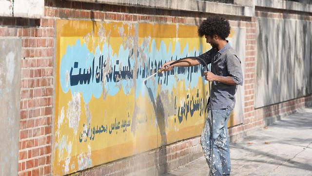Un trabajador utiliza un limpiador de chorro de agua para borrar una pintura mural en la pared de la antigua embajada de EE. UU. En Teherán, 29 de septiembre de 2019