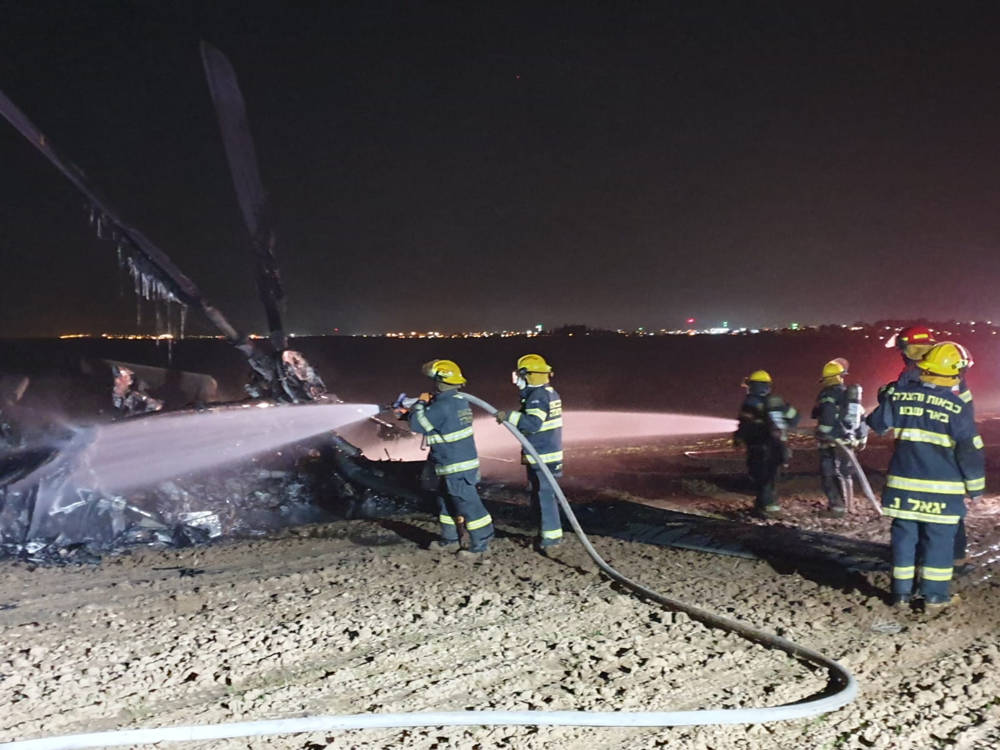 Los bomberos trabajan para extinguir un incendio en un helicóptero que realizó un aterrizaje de emergencia en un campo en las afueras de Rahat en el desierto de Negev el 26 de noviembre de 2019. (Servicios de bomberos y rescate)