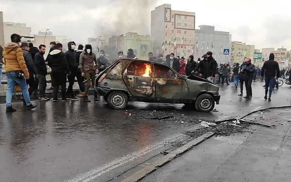 Manifestantes iraníes se reúnen alrededor de un automóvil en llamas durante una manifestación contra un aumento de los precios de la gasolina, en la capital, Teherán, el 16 de noviembre de 2019. (AFP)