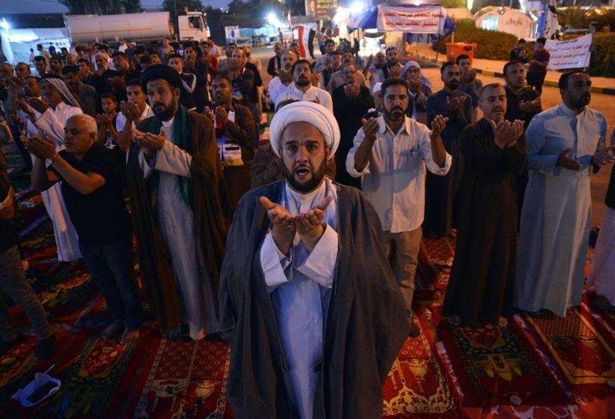 Los manifestantes iraquíes participan en oraciones colectivas durante las manifestaciones antigubernamentales en curso en la ciudad central del santuario sagrado de Najaf, el 10 de noviembre de 2019. (Haidar Hamdani / AFP)