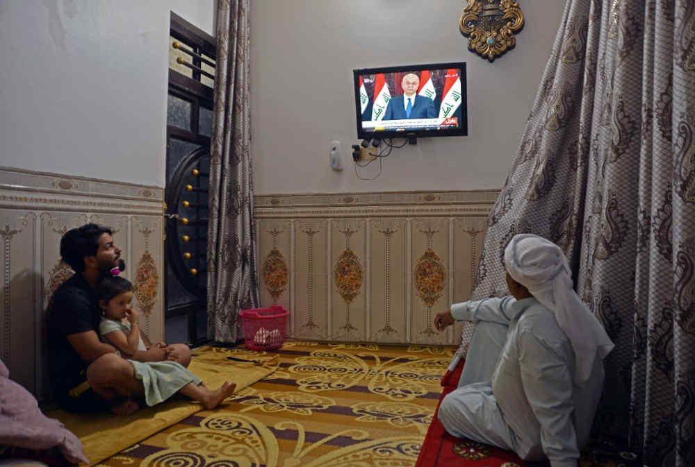 Los iraquíes miran un discurso televisado del presidente de Iraq, Barham Saleh, en la ciudad central del santuario de Najaf el 31 de octubre de 2019. (Foto de Haidar HAMDANI / AFP)