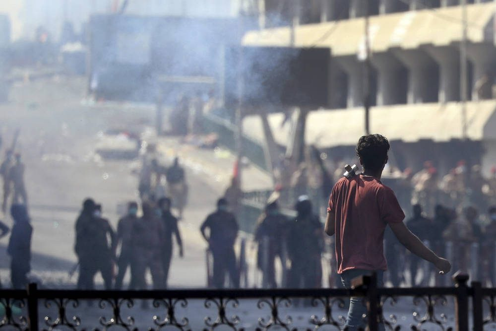 La policía antidisturbios iraquí dispara gases lacrimógenos para dispersar a los manifestantes antigubernamentales reunidos en el puente en el centro de Bagdad, Iraq, 9 de noviembre de 2019. (Foto AP / Hadi Mizban)
