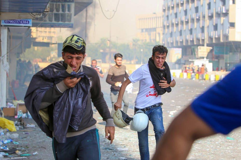 Los manifestantes iraquíes se refugian en gases lacrimógenos disparados por las fuerzas de seguridad en la plaza al-Khalani en el centro de Bagdad el 10 de noviembre de 2019. (Sabah Arar / AFP)