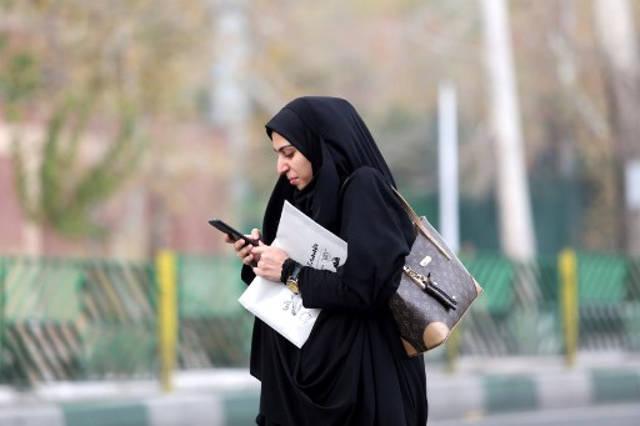 Una mujer usa un teléfono inteligente mientras está de pie en una calle de la capital iraní, Teherán, el 23 de noviembre de 2019. - Los iraníes han estado luchando por adaptarse a la vida fuera de línea casi una semana en un apagón de Internet casi total impuesto en medio de manifestaciones violentas que han obligado a algunos a recurrir a las viejas formas de sobrevivir. (Foto por ATTA KENARE / AFP)