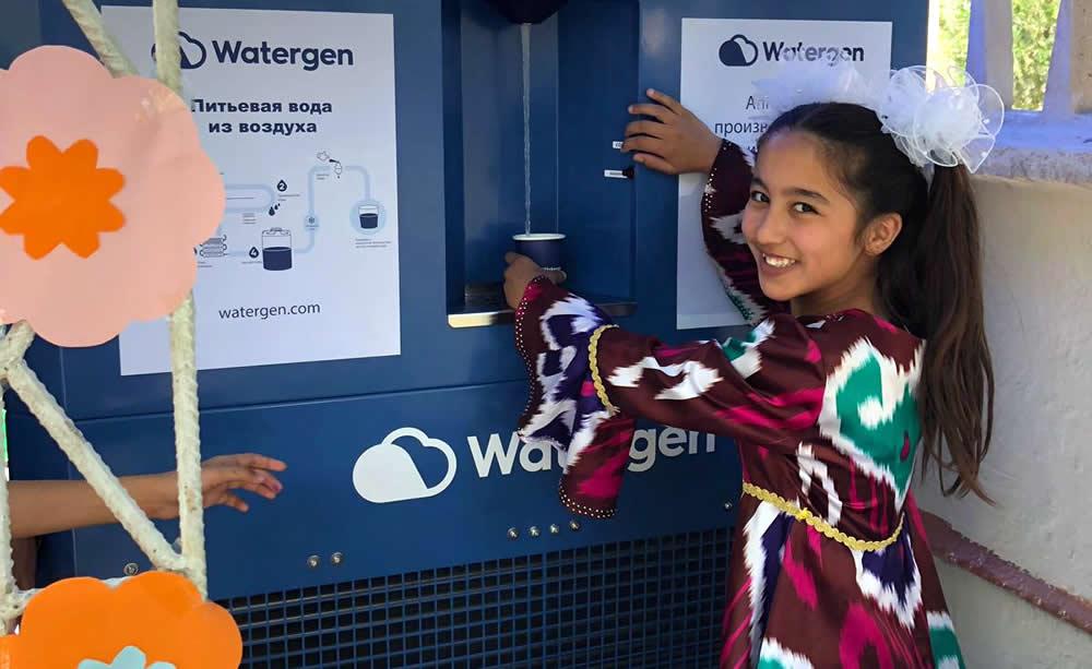 """Una niña en Bukhara, Uzbekistán, toma muestras de agua de un generador de agua atmosférica conocido como """"GEN-350"""", mayo de 2019. Crédito: Watergen."""