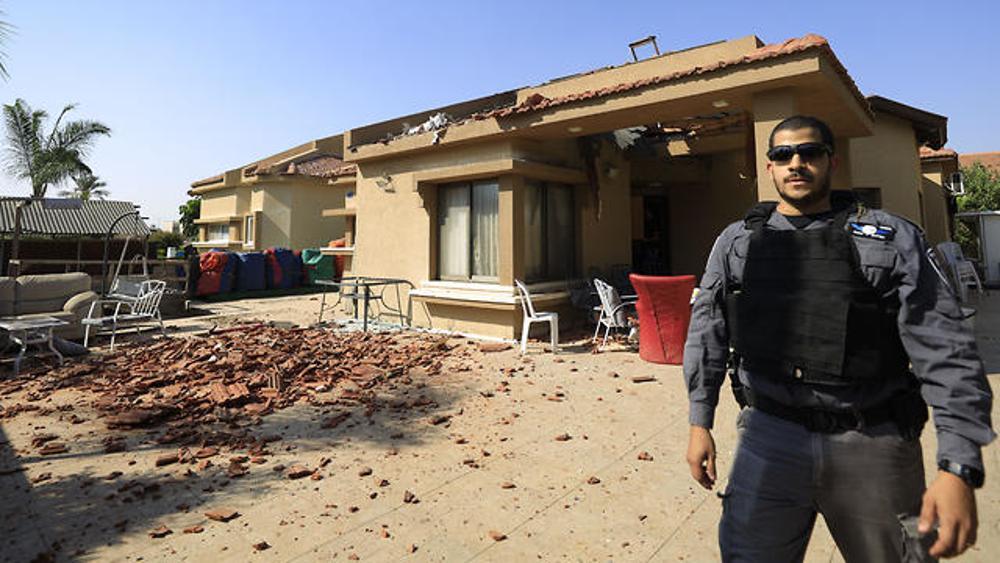 Un policía se para frente a una casa impactada por un cohete de Gaza en la ciudad sureña de Netivot, el 12 de noviembre de 2019.