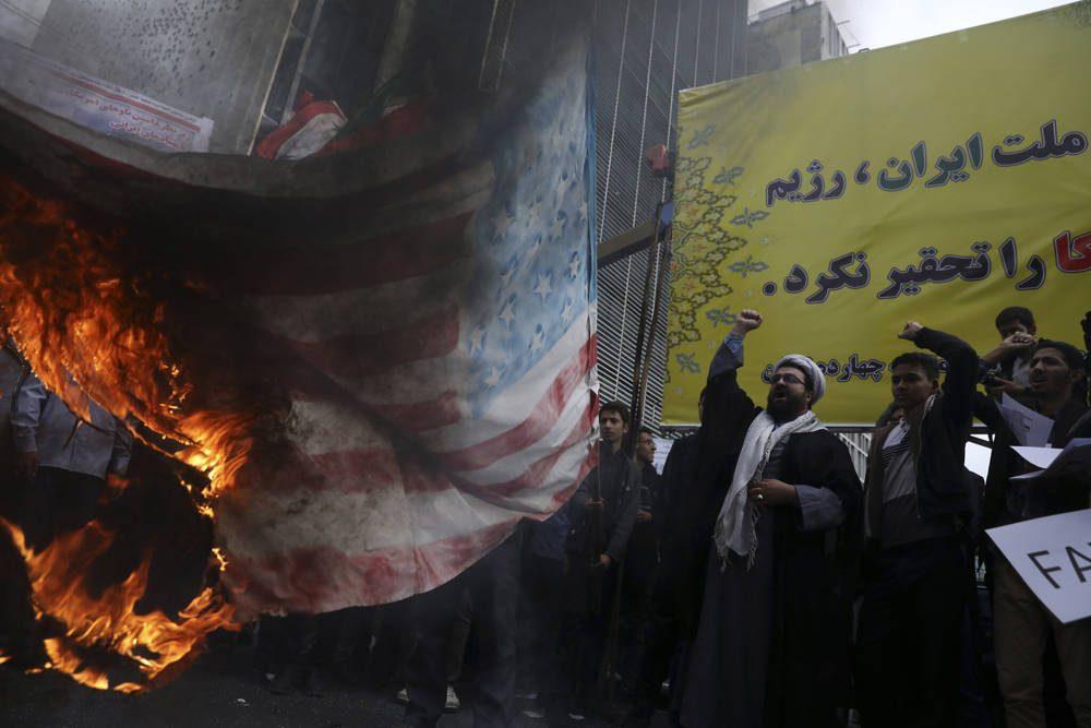 Los manifestantes iraníes cantan consignas mientras prendieron fuego a una bandera estadounidense improvisada durante una manifestación anual frente a la antigua Embajada de los Estados Unidos en Teherán, Irán, el 4 de noviembre de 2019 (AP Photo / Vahid Salemi)