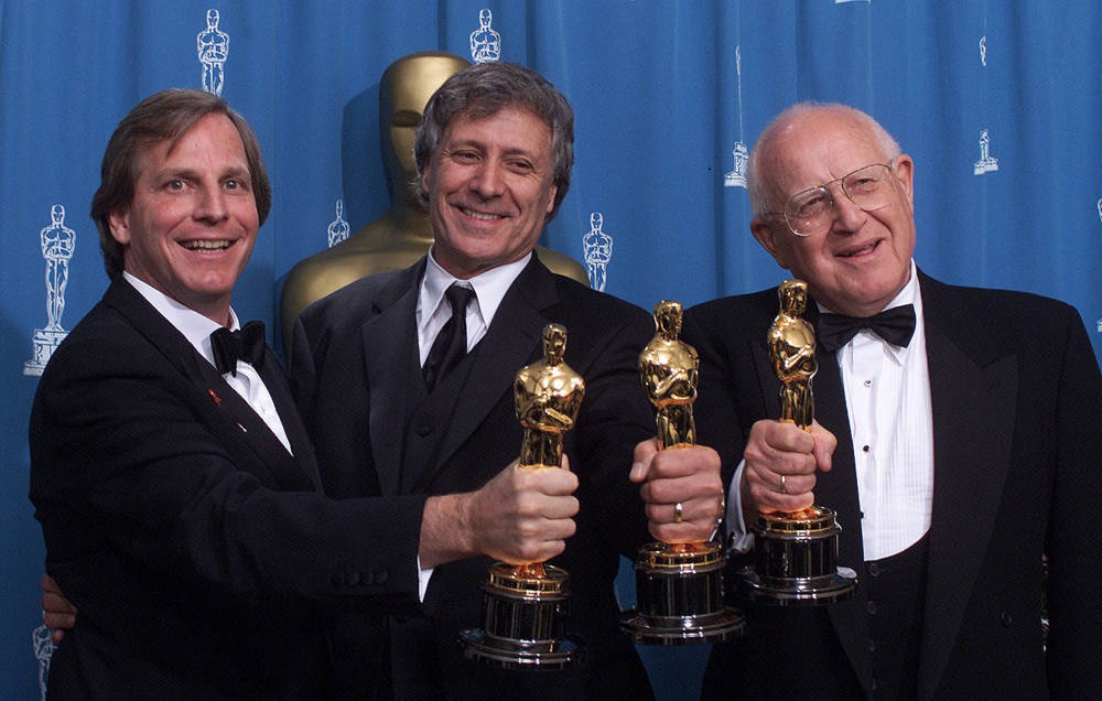 """De izquierda a derecha: Douglas Wick, David Franzoni y Branko Lustig celebran sus Oscar detrás del escenario en el Auditorio Shrine de Los Ángeles, el 25 de marzo de 2001, después de que """"Gladiator"""" fue galardonado como mejor película del año por la Academia de Artes y Ciencias Cinematográficas. (Foto AP / Richard Drew)"""