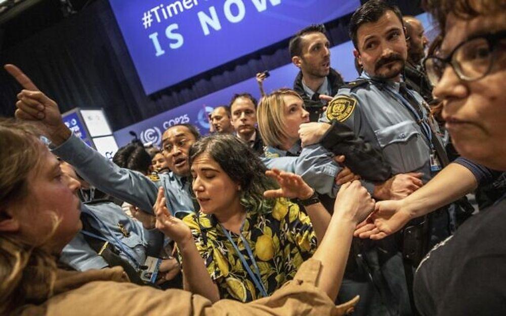 Los manifestantes se pelean con los miembros del personal de seguridad de la ONU durante una protesta en la cumbre COP25 en Madrid, 11 de diciembre de 2019. (Foto AP / Bernat Armangue)