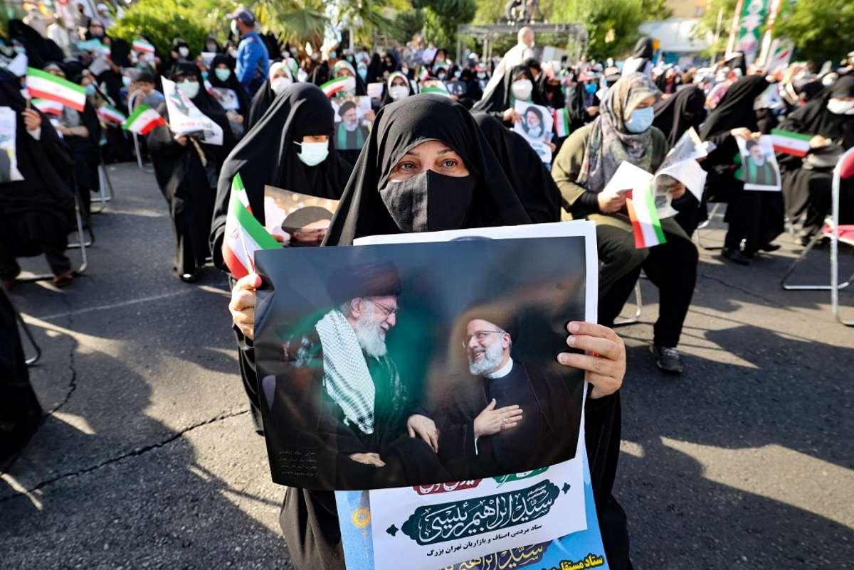 Un partidario del candidato presidencial ultraconservador iraní Ebrahim Raisi lleva un cartel con una foto suya con el líder supremo de Irán, el ayatolá Alí Jamenei, durante un mitin en la capital, Teherán, el 16 de junio de 2021 (ATTA KENARE / AFP)