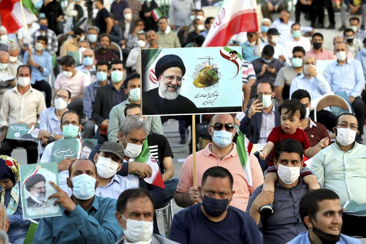 Simpatizantes del candidato presidencial Ebrahim Raisi sostienen carteles durante un mitin en Teherán, Irán, el 14 de junio de 2021. (Ebrahim Noroozi/AP)