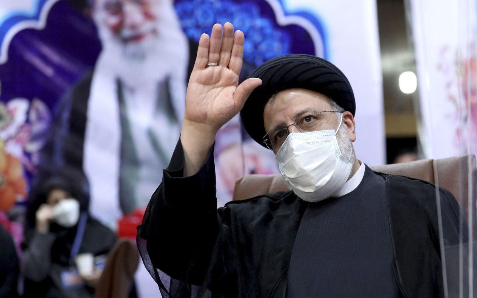 Ebrahim Raisi, jefe del poder judicial iraní, saluda a los periodistas mientras registra su candidatura para las elecciones presidenciales, en Teherán, Irán, el 15 de mayo de 2021. Detrás de él hay un cartel del líder supremo, el ayatolá Alí Jamenei. (AP Photo/Ebrahim Noroozi, Archivo)