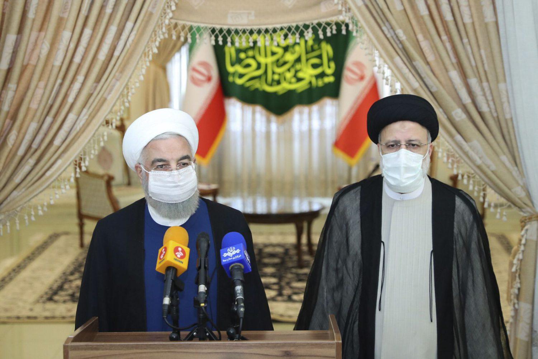 En esta foto publicada por el sitio web oficial de la oficina de la Presidencia iraní, el presidente Hassan Rouhani, a la izquierda, habla con los medios de comunicación después de su reunión con el presidente electo Ebrahim Raisi, a la derecha, que es el actual jefe del poder judicial, en Teherán, Irán, el 19 de junio de 2021 (Oficina de la Presidencia iraní vía AP)