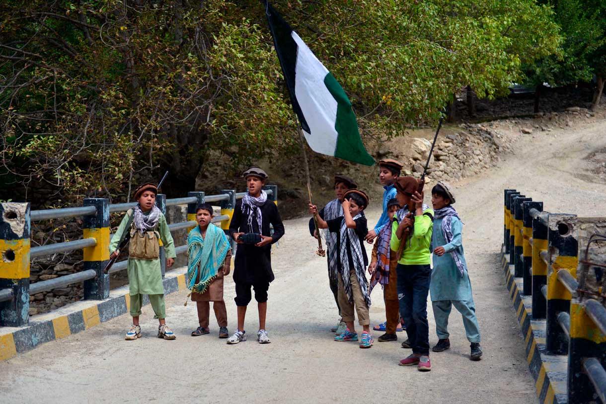 Niños de residentes afganos locales portando rifles de caza y una bandera sobre un puente en el área de Bandejoy del distrito de Dara, en la provincia de Panjshir, el 21 de agosto de 2021, días después de la sorprendente toma de posesión de Afganistán por parte de los talibanes. (Ahmad SAHEL ARMAN / AFP)