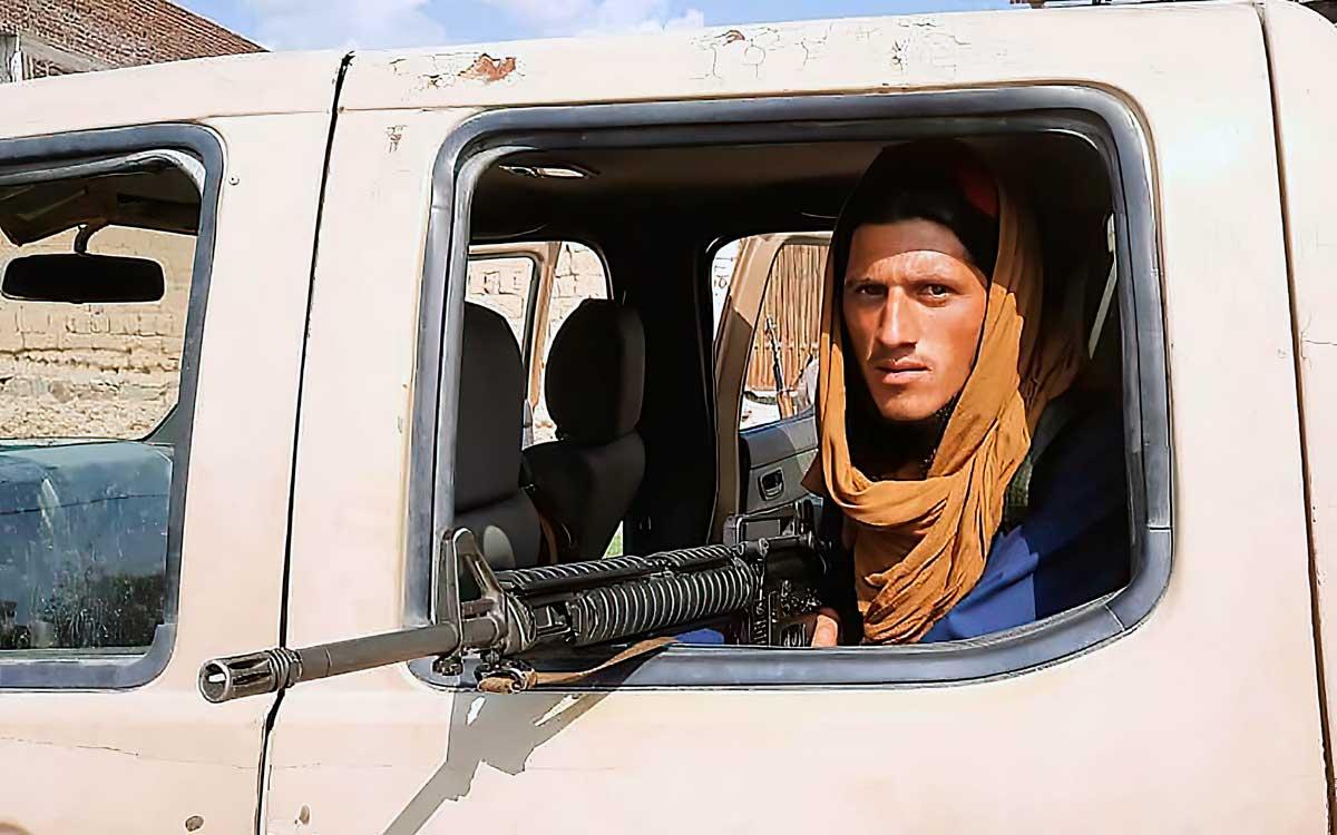 Un combatiente talibán sentado dentro de un vehículo del Ejército Nacional Afgano (ANA) al borde de la carretera en la provincia de Laghman el 15 de agosto de 2021. (AFP)