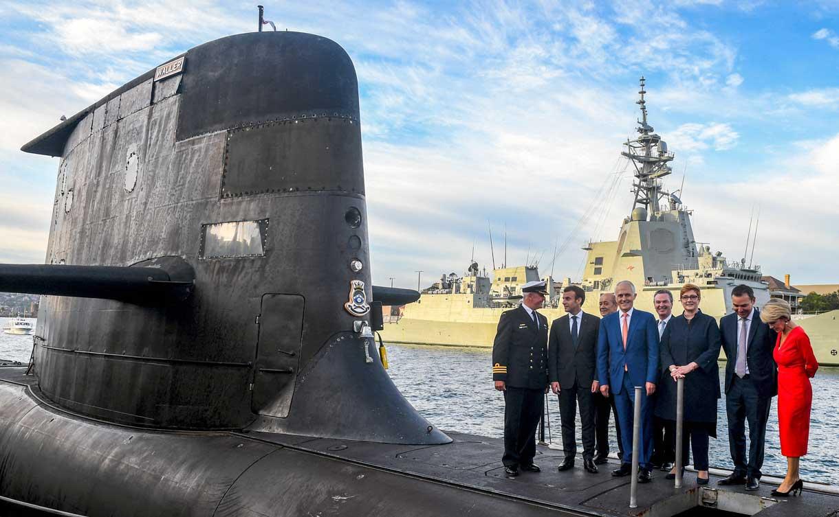 Una foto de archivo tomada el 2 de mayo de 2018 muestra al presidente francés Emmanuel Macron (2/L) y al primer ministro australiano Malcolm Turnbull (C) de pie en la cubierta del HMAS Waller, un submarino de clase Collins operado por la Royal Australian Navy, en Garden Island en Sídney. (Foto de BRENDAN ESPOSITO / POOL / AFP)