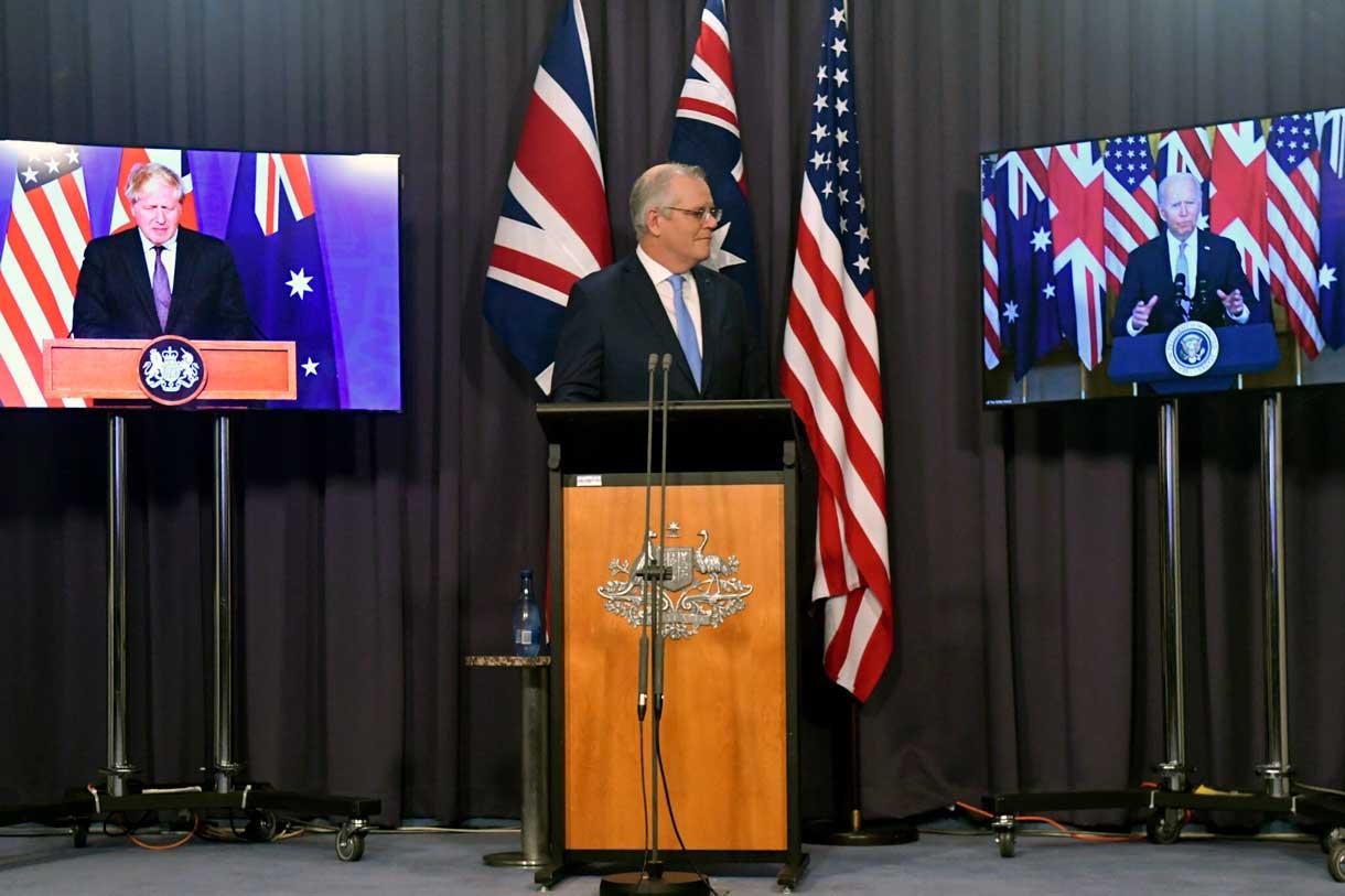 El primer ministro de Australia, Scott Morrison, en el centro, aparece en el escenario con enlaces de vídeo con el primer ministro de Gran Bretaña, Boris Johnson, a la izquierda, y el presidente de Estados Unidos, Joe Biden, en una conferencia de prensa conjunta en la Casa del Parlamento en Canberra, el jueves 16 de septiembre de 2021. Los líderes anuncian una alianza de seguridad que permitirá un mayor intercambio de capacidades de defensa, incluyendo la ayuda para equipar a Australia con submarinos de propulsión nuclear. (Mick Tsikas/AAP Image vía AP)