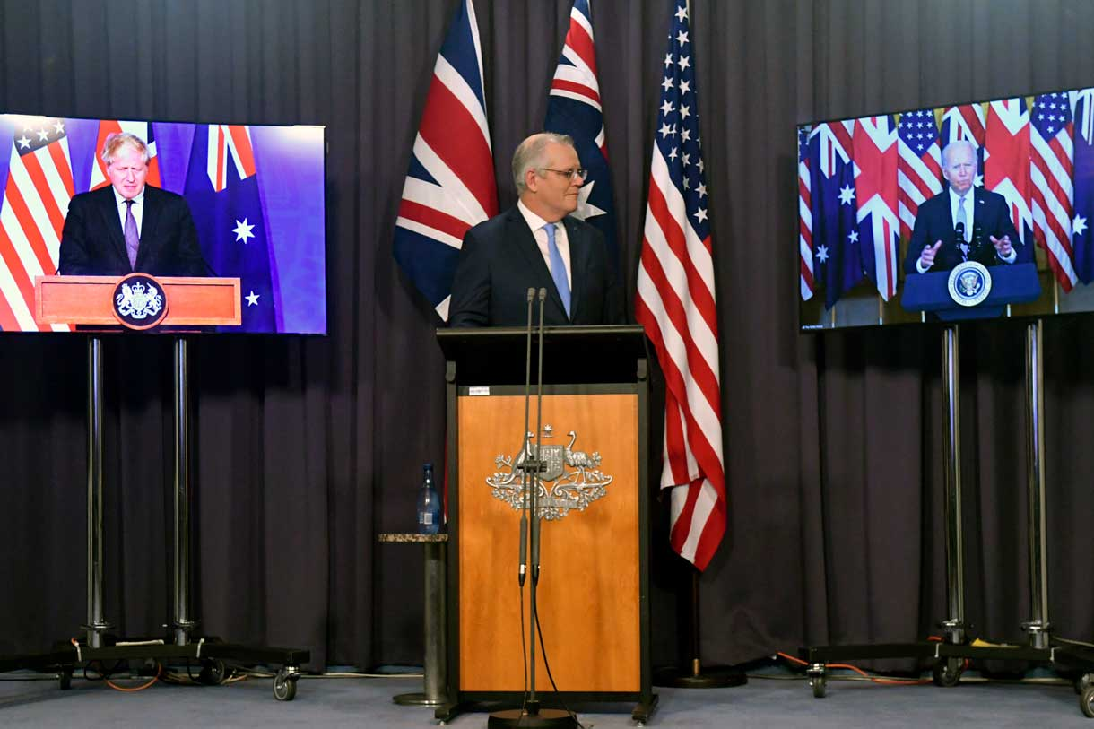 El primer ministro de Australia, Scott Morrison, en el centro, aparece en el escenario con enlaces de vídeo con el primer ministro de Gran Bretaña, Boris Johnson, a la izquierda, y el presidente de Estados Unidos, Joe Biden, en una conferencia de prensa conjunta en la Casa del Parlamento en Canberra, el 16 de septiembre de 2021. (Mick Tsikas/AAP Image vía AP)