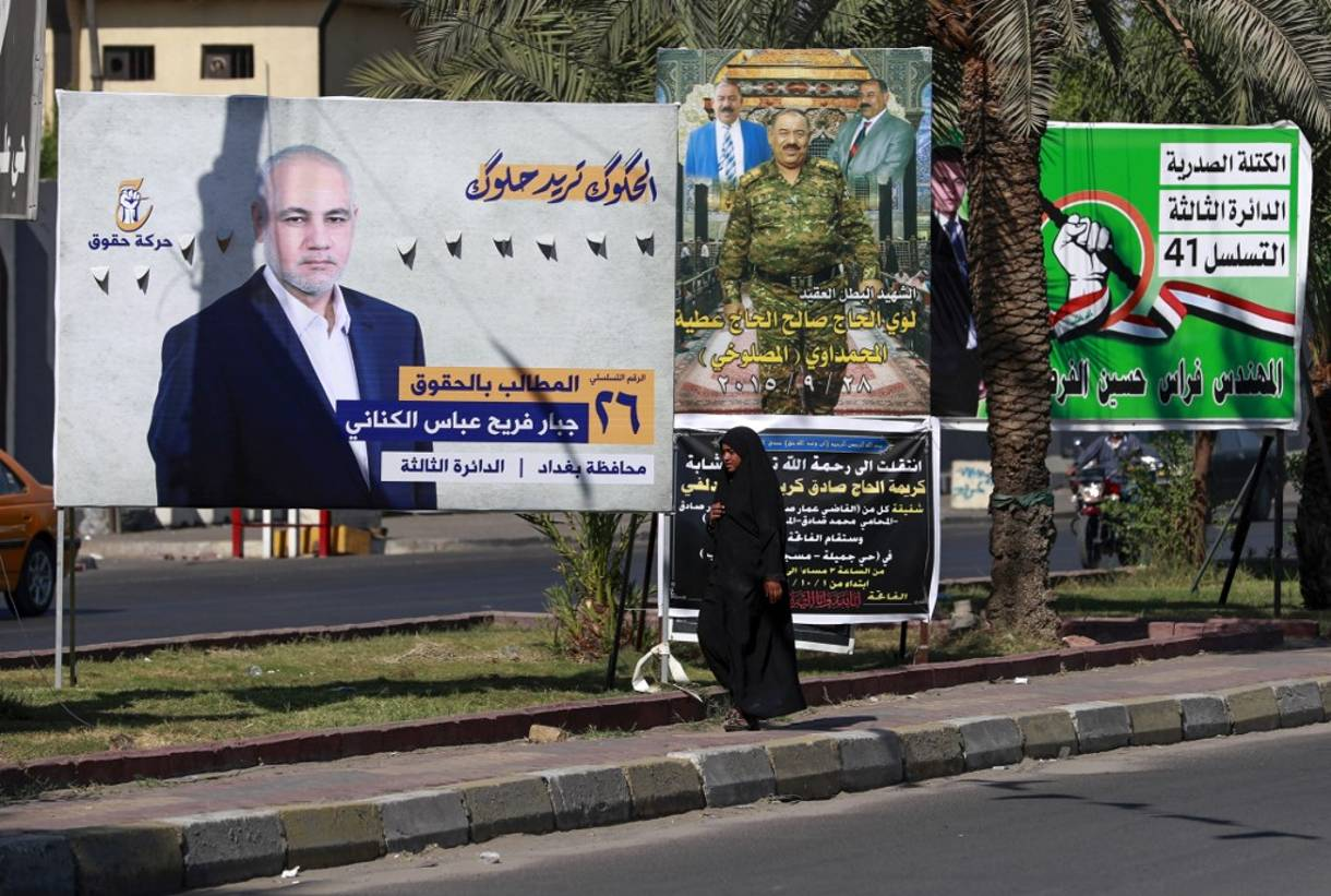 Una mujer iraquí camina delante de los carteles electorales de los candidatos a las próximas elecciones parlamentarias, en el barrio de Ciudad Sadr de la capital, Bagdad, el 9 de octubre de 2021. (AHMAD AL-RUBAYE / AFP)